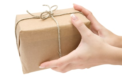 Female hands holding a brown parcel. Isolated on a white background.